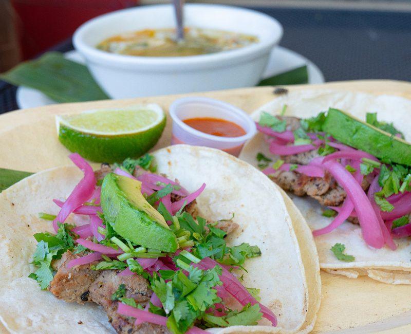 tacos de poc chuc on a plate with salsa and a lime